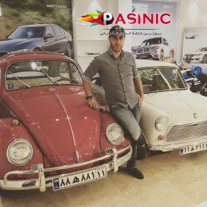 علی کریمی در کنار دو ماشین قدیمی